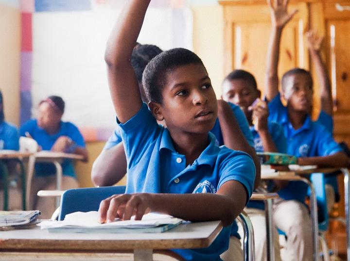 Child in class raising hand