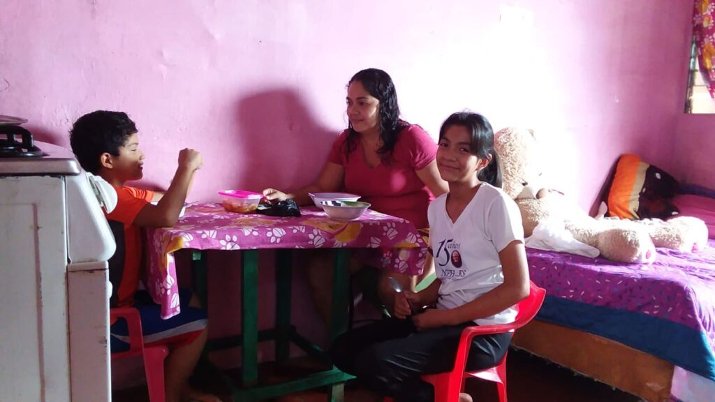Three people eating a meal in a simple home