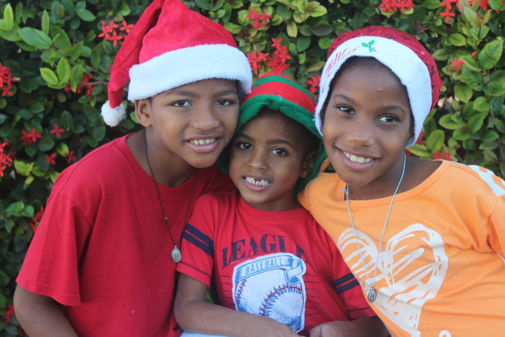 Three smiling children wearing Christmas hats